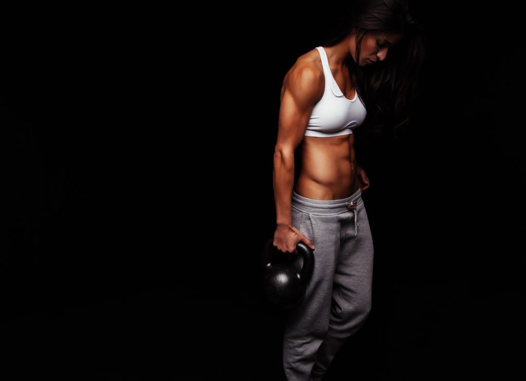 Muscular woman doing crossfit exercise with kettle bell