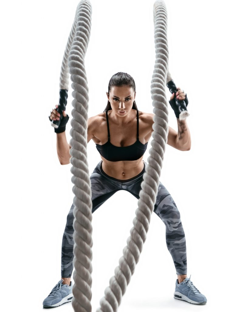 Strong muscular woman working out with heavy ropes.